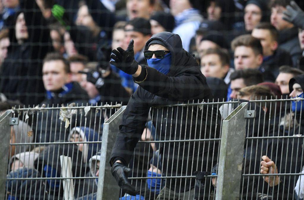 Ein Fan gestikuliert nach dem Spiel in Richtung von Polizeibeamten, die auf dem Feld stehen. Foto: dpa