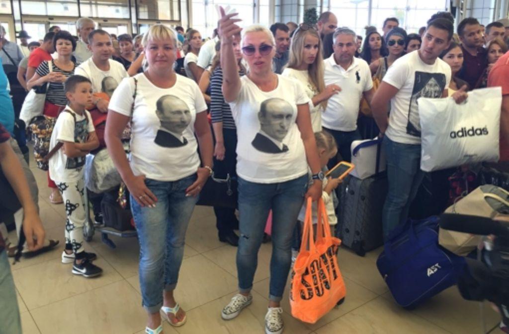 Zwei Russinnen  mit einem Porträt von Präsident Wladimir Putin auf der Brust warten vor der Sicherheitskontrolle am Flughafen von Scharm el Scheich auf die Abfertigung. Foto: dpa