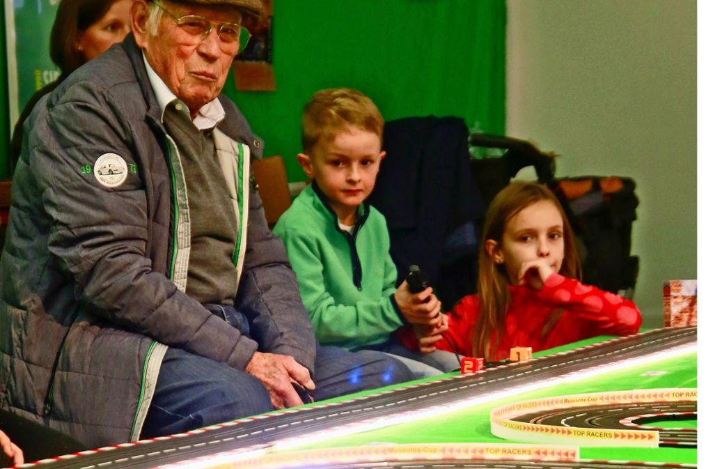Ein Altersunterschied von 85 Jahren und doch die selbe Leidenschaft: Herbert Linge (90) und Lenni Keck (5) duellieren sich an der Carrera-Bahn. Foto: factum/Granville