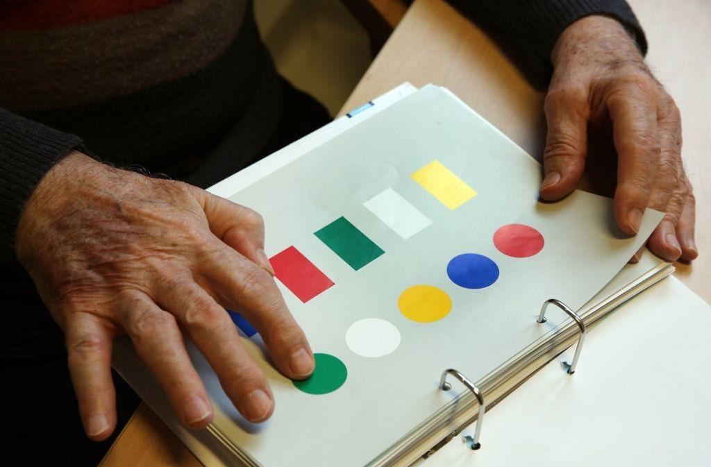 Ein älterer Patient bestimmt Farben und Formen. Aus Sicht von Experten müssen Demenzpatienten viel früher behandelt werden. Foto: dpa