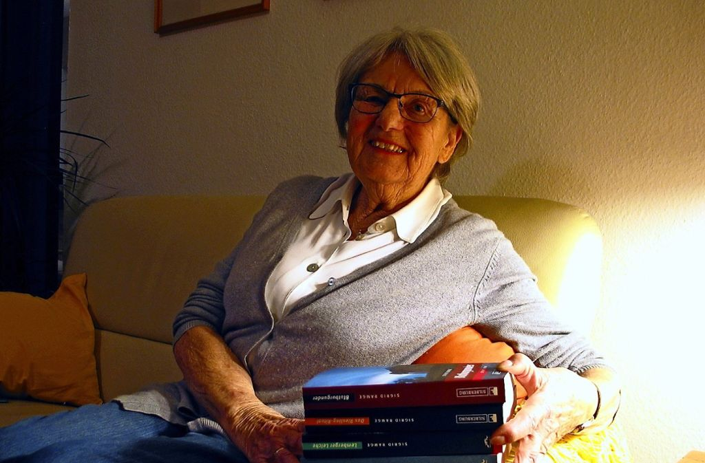 """Sigrid Ramge auf dem heimischen Sofa mit einem Stapel eigener Bücher. Das neueste heißt """"Blutburgunder"""". Foto: /Susanne Müller-Baji"""