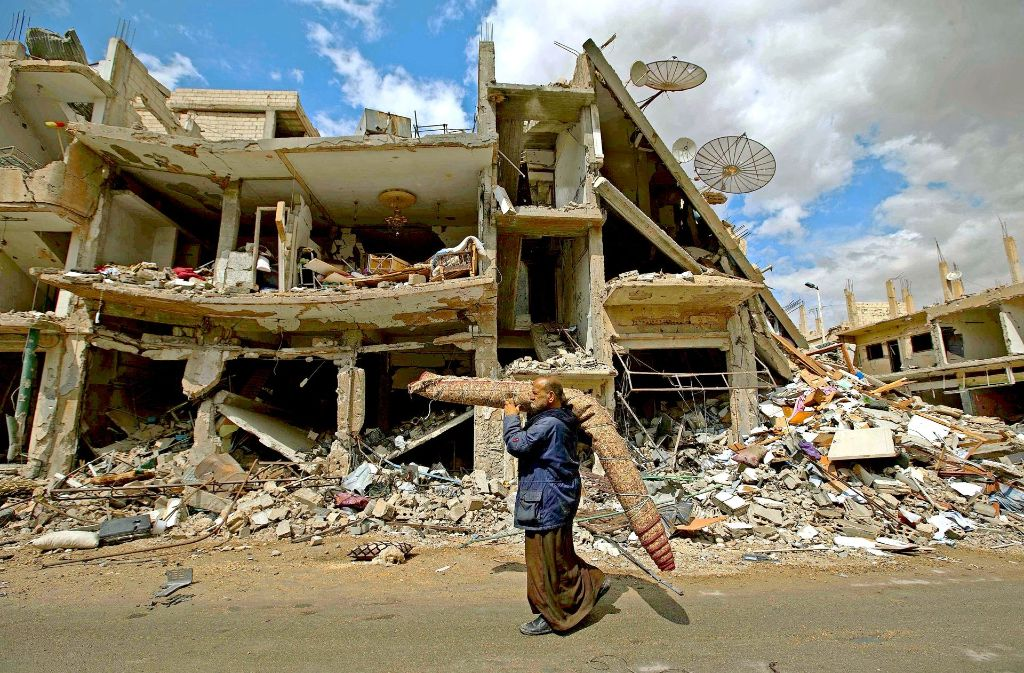 Dieser Mann rettet seine  letzten Habseligkeiten in Palmyra (Provinz Homs) Foto: AP