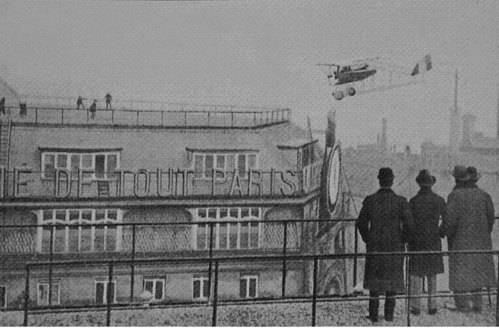 Ein Fotograf hält das waghalsige Luftmanöver von Jules Védrines am 19. Januar 1919 mitten in Paris mit seiner Kamera für die Nachwelt fest. Foto: Wikipedia commons/Inconnu/BM Reims