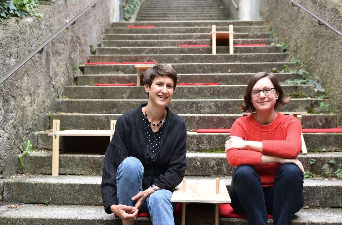 Sabine Fessler (links) und Christina Schmid sitzen auf einem Stäffele. In der Mitte ein eigens gefertigter Tisch zum Verweilen auf der Treppe. Foto: /Marion Jäger