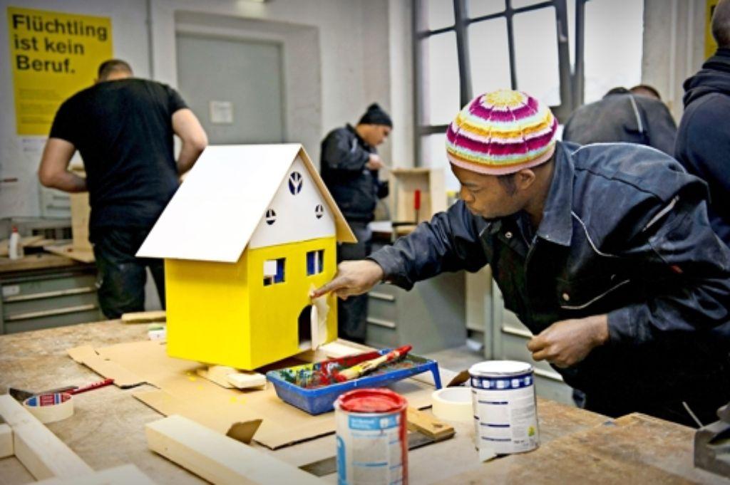 Ein Mann aus Ghana lernt bei einem Projekt der Handwerkskammer in Berlin im Kleinen, wie man Häuser streicht. Foto: imago