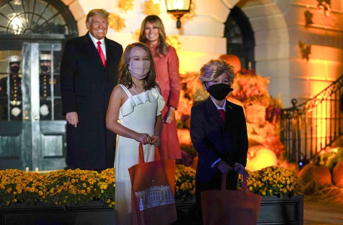 Donald und Melania Trump posieren für ein Foto mit zwei Kindern, die sich als der Präsident und die First Lady verkleidet haben. Foto: AP/Manuel Balce Ceneta