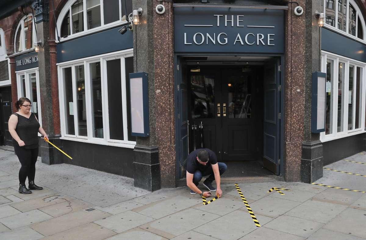 """Mitarbeiter des Pubs """"The Long Acre"""" markieren vor dem Eingang mit Klebeband den während der Corona-Pandemie getrennten Eingangs- und Ausgangsbereich Foto: dpa/Frank Augstein"""