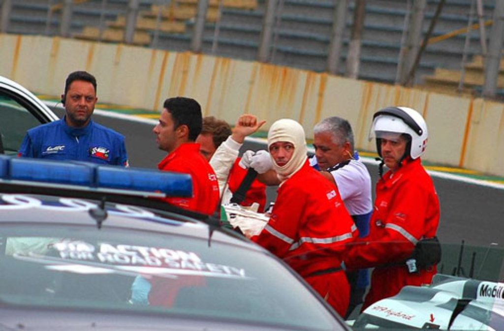 Nach seinem schweren Unfall in Sao Paulo reckt Mark Webber den Daumen in die Höhe, als er auf einer Trage abtransportiert wird. Foto: dpa