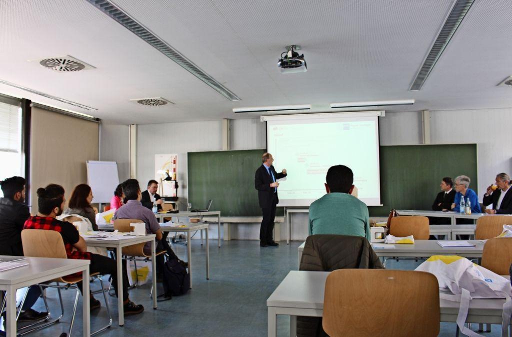 DHBW-Studiengangleiter Harald Stuhler erläutert den Flüchtlingen das Konzept. Foto: DHBW