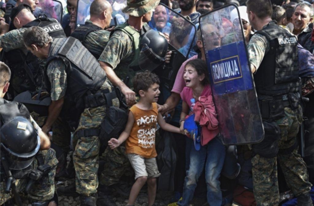 Zwei Kinder an der griechisch-mazedonischen Grenze zwischen Soldaten und drängelnden Menschenmassen. Foto: