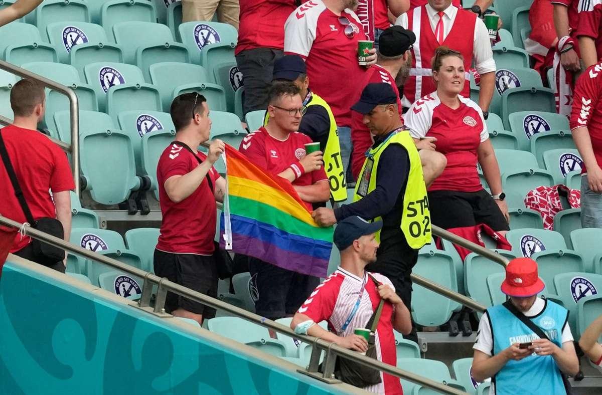 Zwei Ordner wollen diesen dänischen Fans offenbar eine Regenbogen-Fahne abnehmen. Foto: AFP/DARKO VOJINOVIC