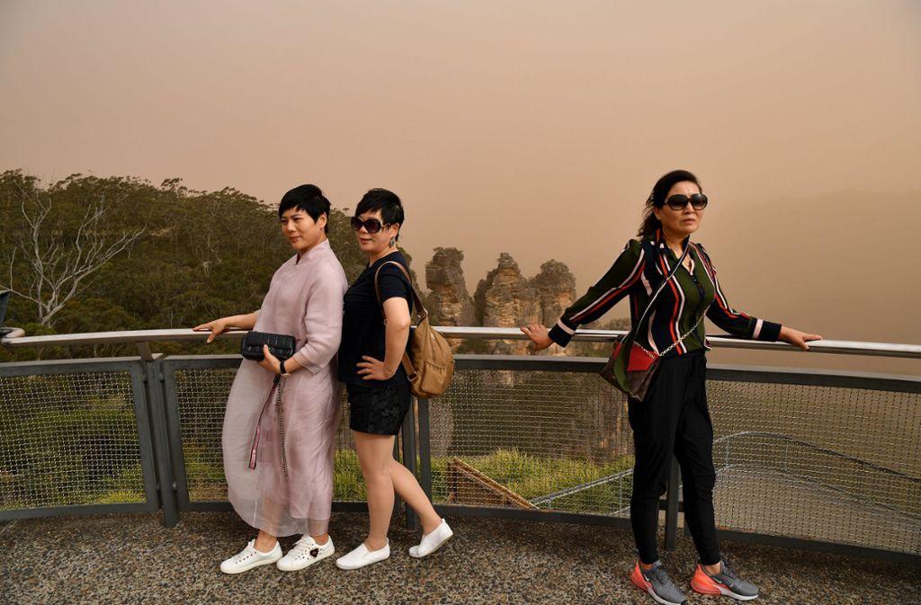 """Seit Tagen wüten Buschfeuer im Osten Australiens: Das beeinträchtigt auch Urlauber, wie diese drei Touristinnen am Aussichtspunkt """"Three Sisters"""". Foto: dpa/Joel Carrett"""