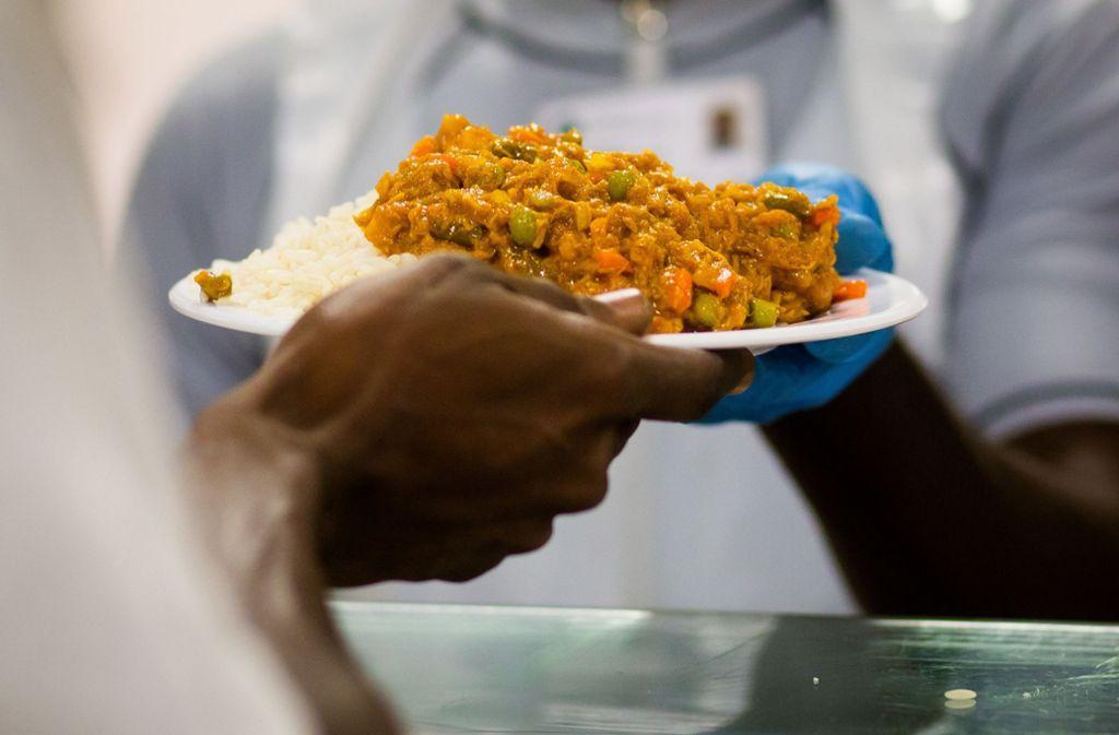 Beim Fastenbrechen in der Landeserstaufnahmeeinrichtung (LEA) in Ellwangen nimmt ein Flüchtling, der an Ramadan teilnimmt, in der Kantine ein Fischgericht mit Reis entgegen. Foto: dpa