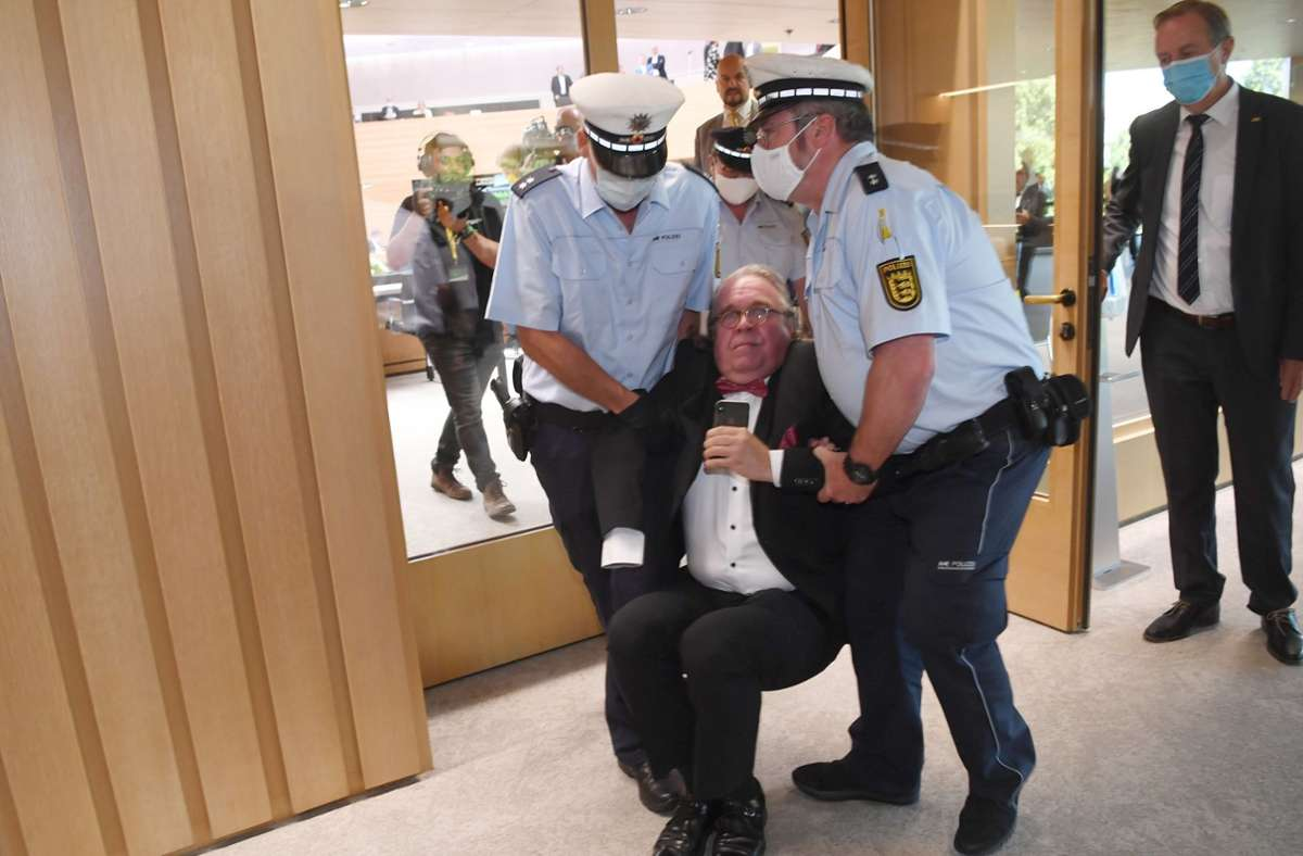 Der Abgeordnete Heinrich Fiechtner wird von zwei Polizisten hinaus getragen. Foto: dpa/Marijan Murat