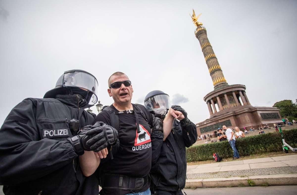 Polizisten führten einen Demonstranten vor der Siegessäule ab. Fortan ist hier täglicher Protest geplant. Foto: dpa/Christoph Soeder