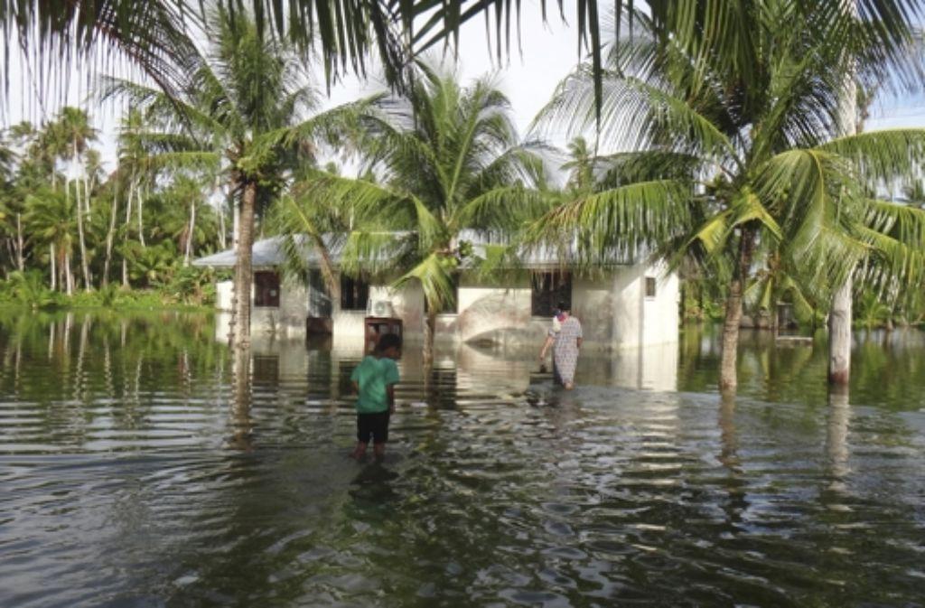 Sie trifft der Klimawandel ganz besonders: Teile der Marshall-Inseln wurden in diesem Jahr schon zwei Mal überschwemmt: hier eine Mutter und ihr Kind vor deren gefluteten Haus auf Kili. Foto: AP