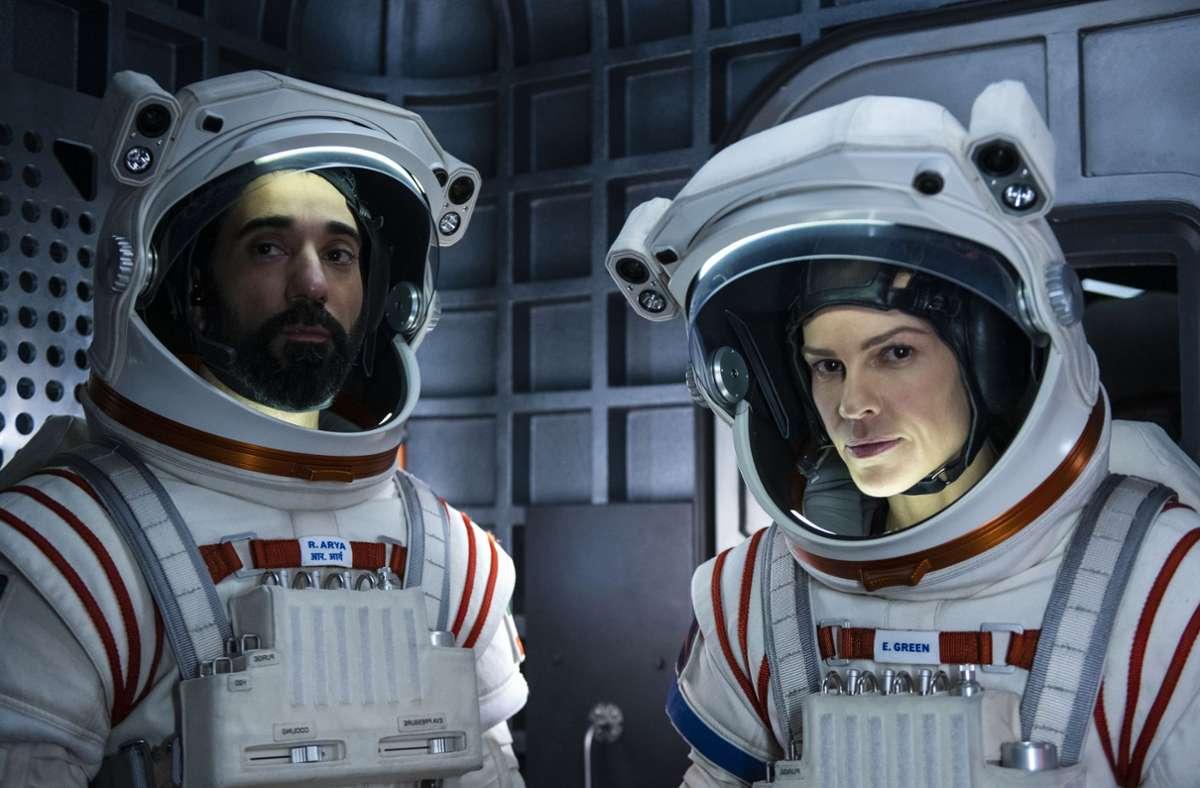 1. Away Die  Astronautin Emma Green (Hilary Swank, rechts, mit Ray Panthaki) fliegt mit einem internationalen Team zum Mars und lässt für lange Zeit Mann und Tochter auf der Erde zurück. Das zehnteilige Science-Fiction-Drama ist nicht als teures Action-Spektakel angelegt, sondern überzeugt als  emotional aufgeladenes Weltraum-Kammerspiel.  Netflix, 4. September Hier geht es zum Trailer Foto: Netflix/Diyah Pera