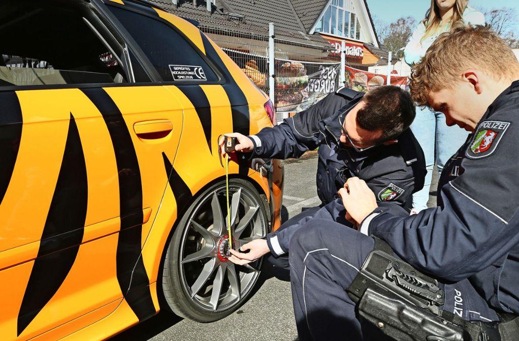 Polizisten kontrollieren ein getuntes Auto bei einem  Tuning-Treffen in Bochum. Foto: dpa