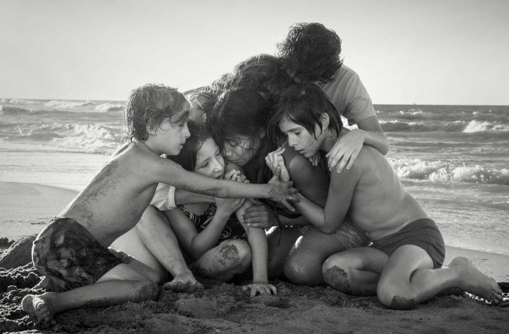 Das Kindermädchen Cleo (Yalitza Aparicio) in inniger und besorgter Umarmung mit Schützlingen am Strand. Foto: Netflix