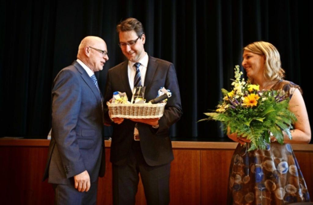 Johannes Fuchs (links) verteilt Präsente mit lokaler Symbolik an Richard Sigel und dessen Gattin. Foto: Gottfried Stoppel