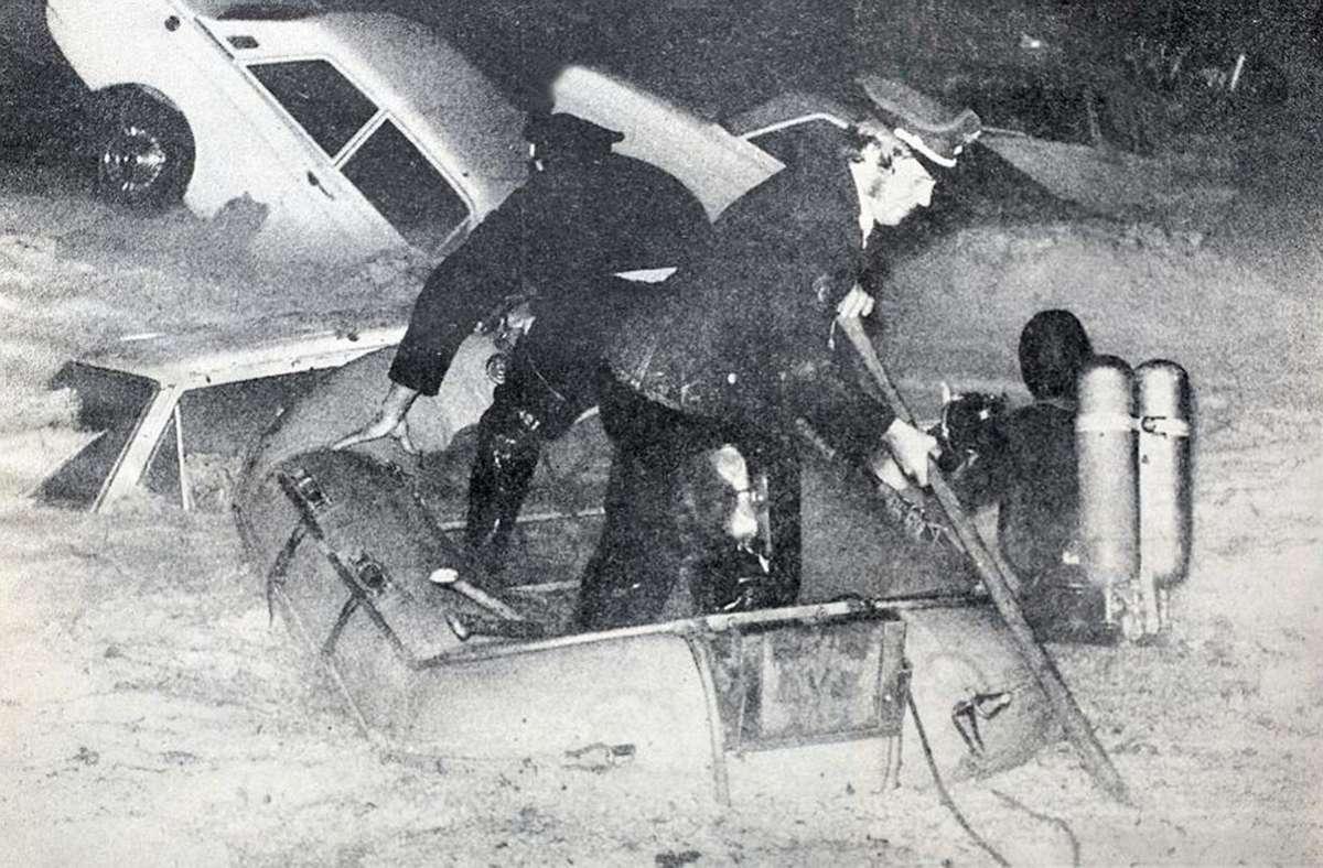 Polizei und Feuerwehr versuchen am 15. August 1972 in Schlauchbooten und mit Tauchern, Autofahrer zu retten.  Foto: Feddersen