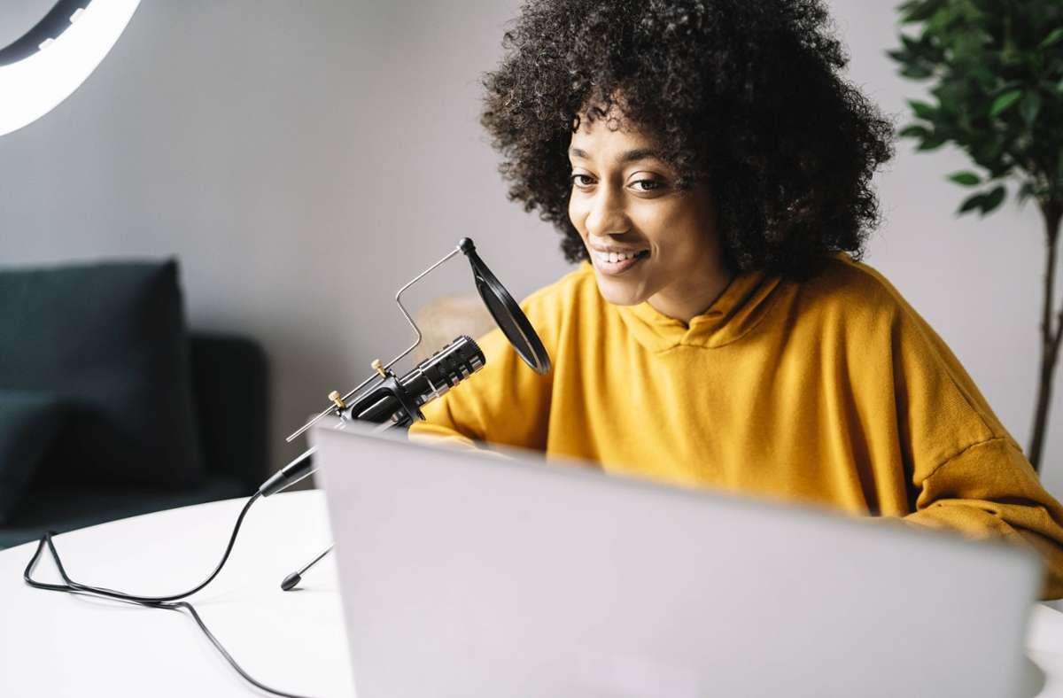 Podcasts können nicht nur in professionellen Studios aufgenommen werden, sondern auch zu Hause vorm Mikrofon – ohne hohe Produktionskosten (Symbolbild). Foto: imago images/Westend61