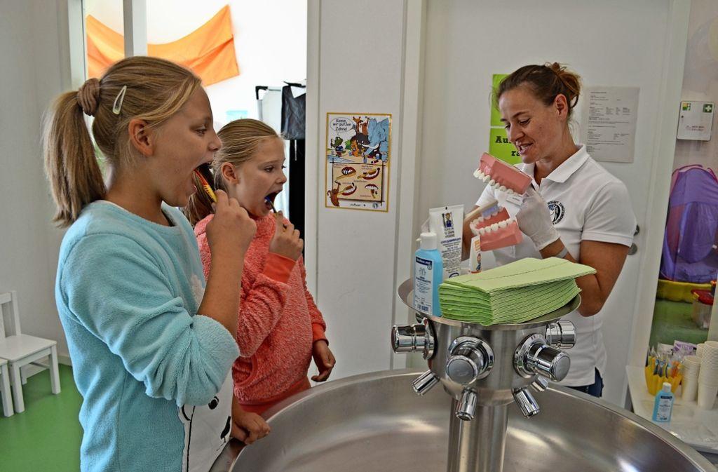 Die Schwestern Xenia und Valeria lernen am Zahnputzbrunnen, wie sie ihre Zähne richtig putzen müssen. Foto: Wiebke Wetschera