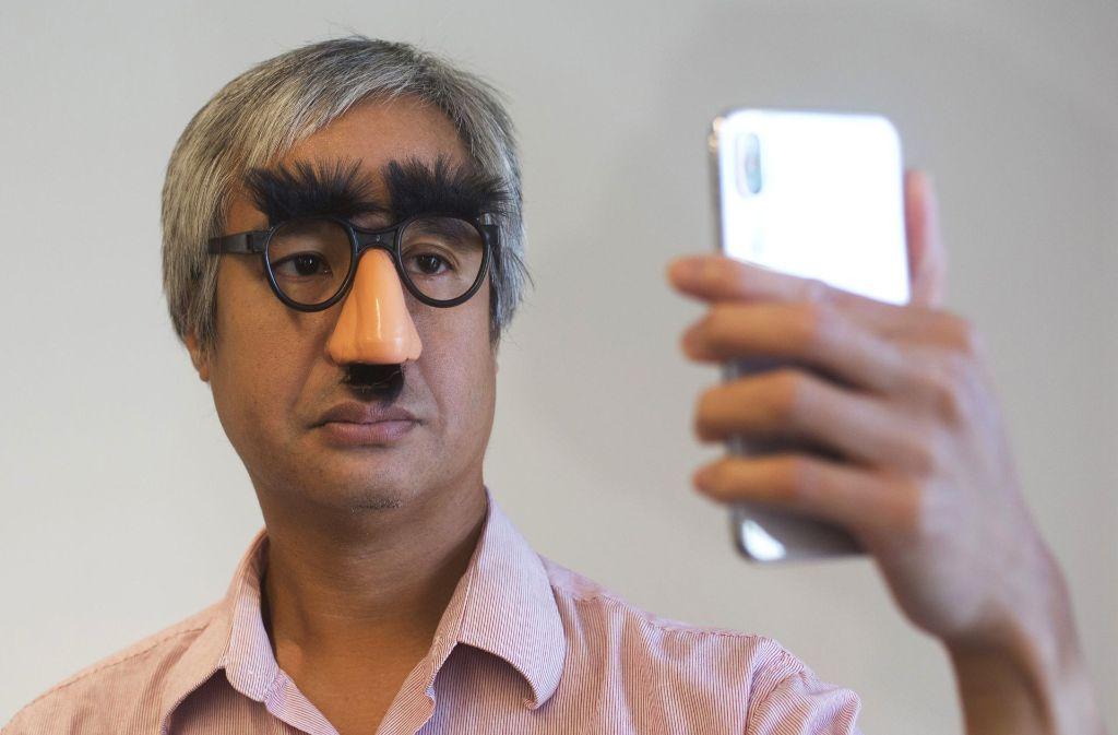 AP-Reporter Anick Jesdanun zeigt, wie das iPhone X auch mit teilweise verdecktem Gesicht noch entsperrt werden kann. Foto: AP