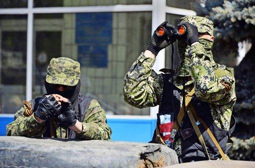 Bewaffnete Männer bewachen einen besetzten Verwaltungsbau in der Ostukraine. Foto: AFP