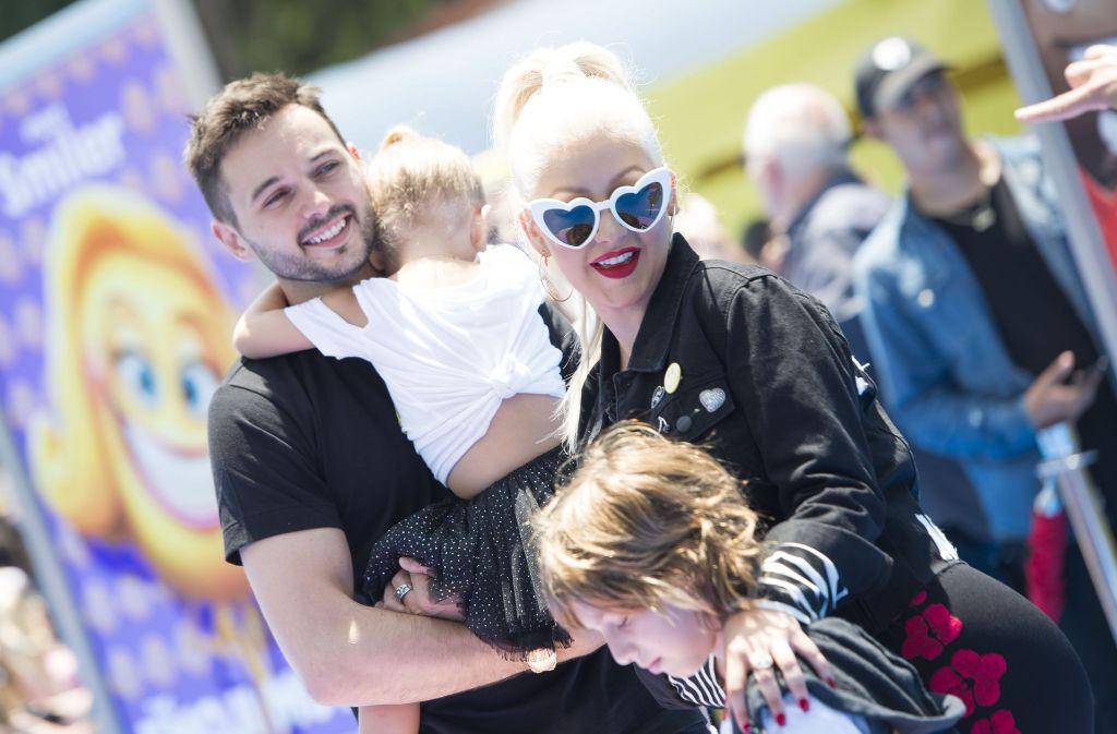 Christina Aguilera mit ihrer Familie: Lebenspartner Matthew Rutler hält Tochter Summer Rain, die Sängerin legt ihren Arm um Sohn Max Liron. Foto: AFP