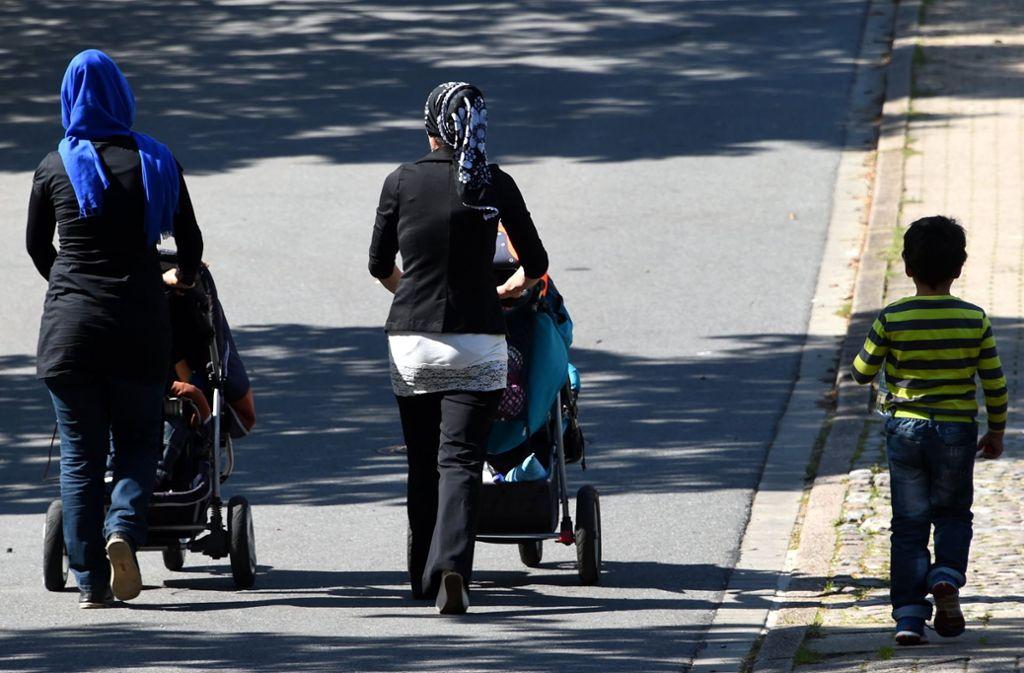 Zwei Frauen mit Kopftüchern schieben ihre Kinderwagen durch Kellinghusen (Schleswig-Holstein). Auch über die Frage, wieweit Kopftuchtragen erlaubt sein soll, wird in Deutschland gestritten. Foto: dpa
