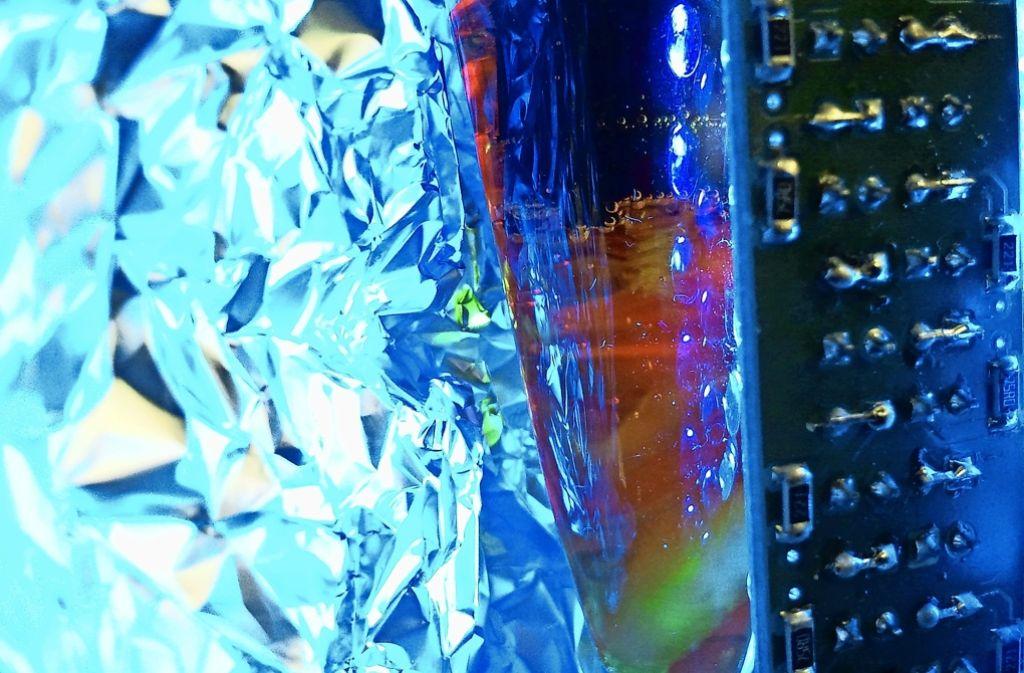 Im Labor der Ulmer Forscher entsteht unter dem Einfluss von Licht aus Wasser Sauerstoff – zu erkennen an den kleinen Gasbläschen im Reaktionsgefäß (Bildmitte). Foto: Universität Ulm