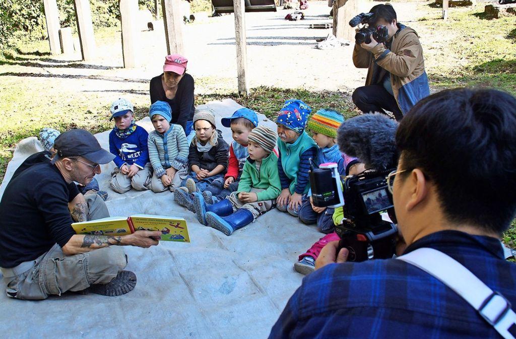Die koreanischen Kameraleute halten fest, wie sich die Wurzelzwerge beim Vorlesen auf einer Lichtung ausruhen. Foto: Leonie Schüler