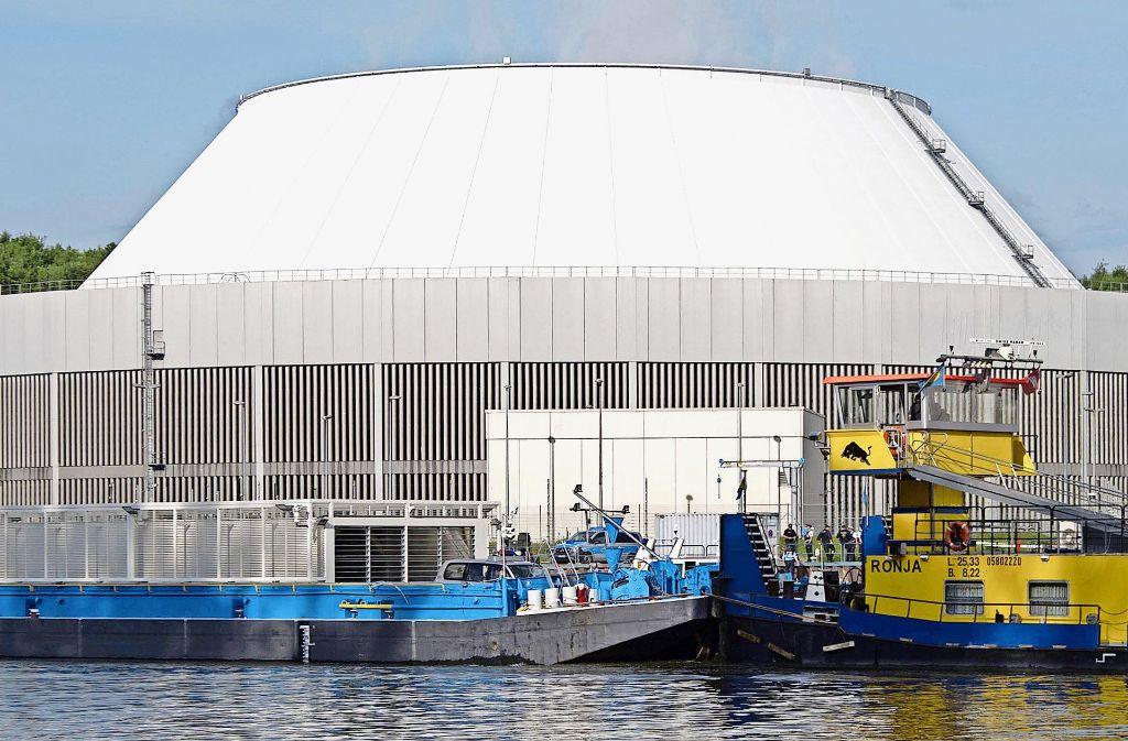 Ein mit radioaktivem Müll beladenes Lastenschiff fährt vor dem Kühlturm des Atomkraftwerks Neckarwestheim. Foto: dpa
