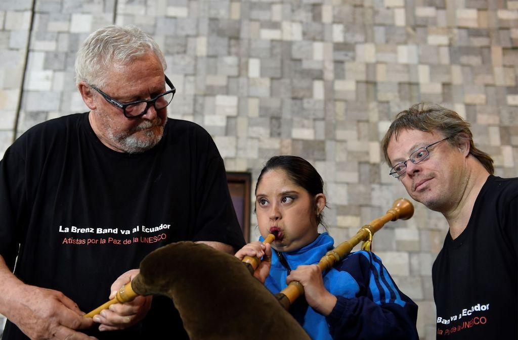 Ein Mitglied des Orquestas Sinamune bekommt von Horst Tögel (li.), Gründer der Brenz Band, und Harald Schmid in Ecuador eine Einführung in die Funktionsweise des Dudelsacks. Foto: Reiner Pfisterer