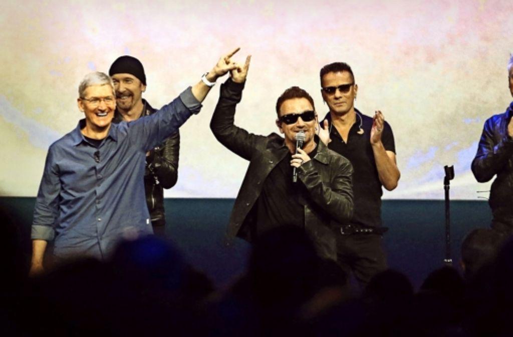 Der Apple-Chef Tim Cook (links) und der Sänger Bono von U2   feiern Hand in Hand ihren Reklame-Coup. Foto: dpa