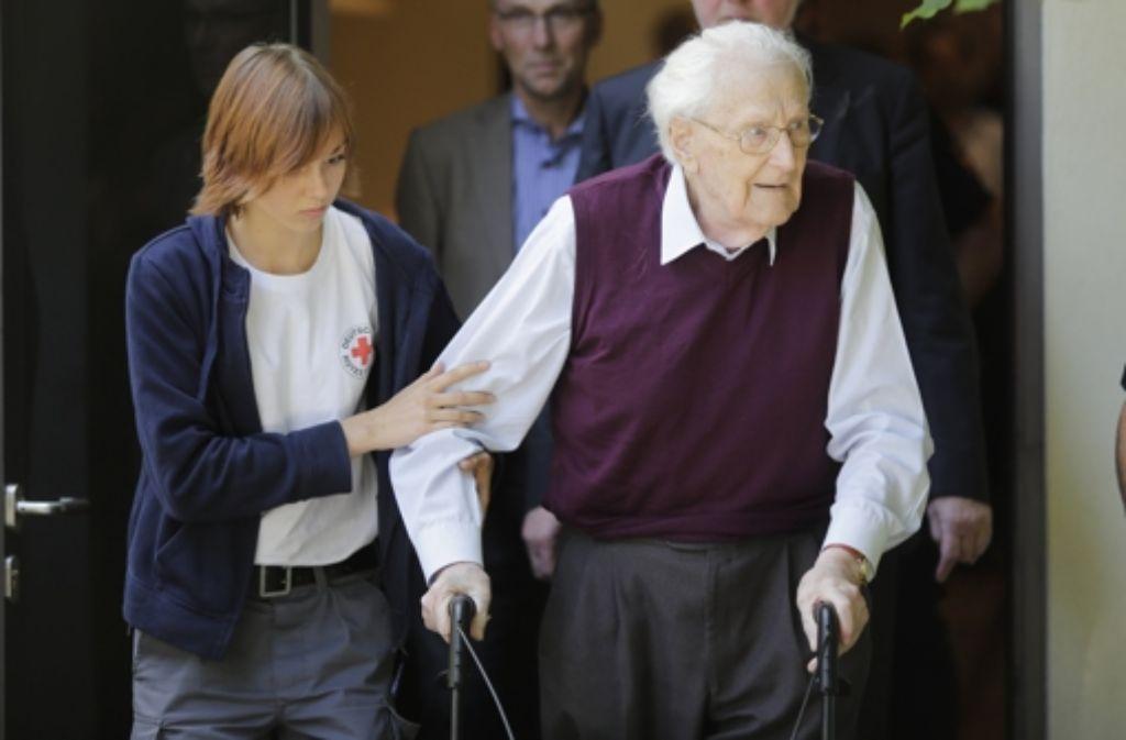Gestützt von einer Rotkreuzhelferin verlässt Oskar Gröning nach dem Richterspruch das Gerichtsgebäude. Der 94-Jährige wurde zu vier Jahren Haft verurteilt. Foto: AP