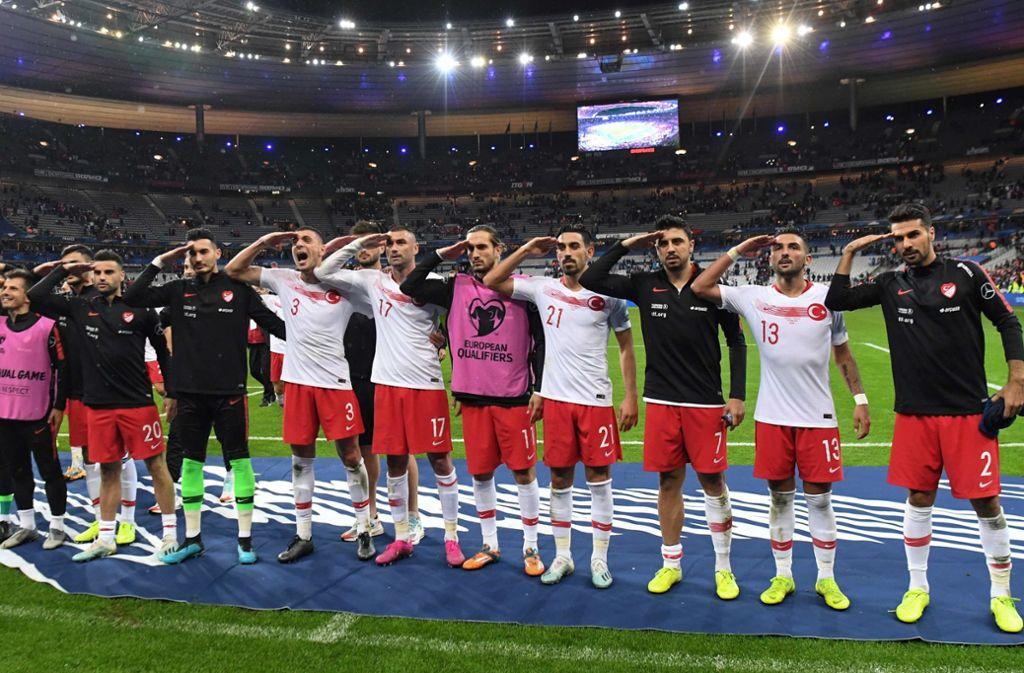 Spieler der türkischen Nationalmannschaft salutieren nach dem EM-Qualifikationsspiel gegen Frankreich im Saint-Denis-Stadion. Foto: AFP/Alain Jocard