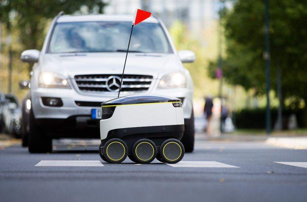 Ein Lieferroboter des Unternehmens Starship Technologies fährt über einen Zebrastreifen. Im Hintergrund ist ein Mercedes zu sehen. Der Autobauer Daimler ist bei dem Entwickler von Lieferrobotern eingestiegen. Foto: dpa