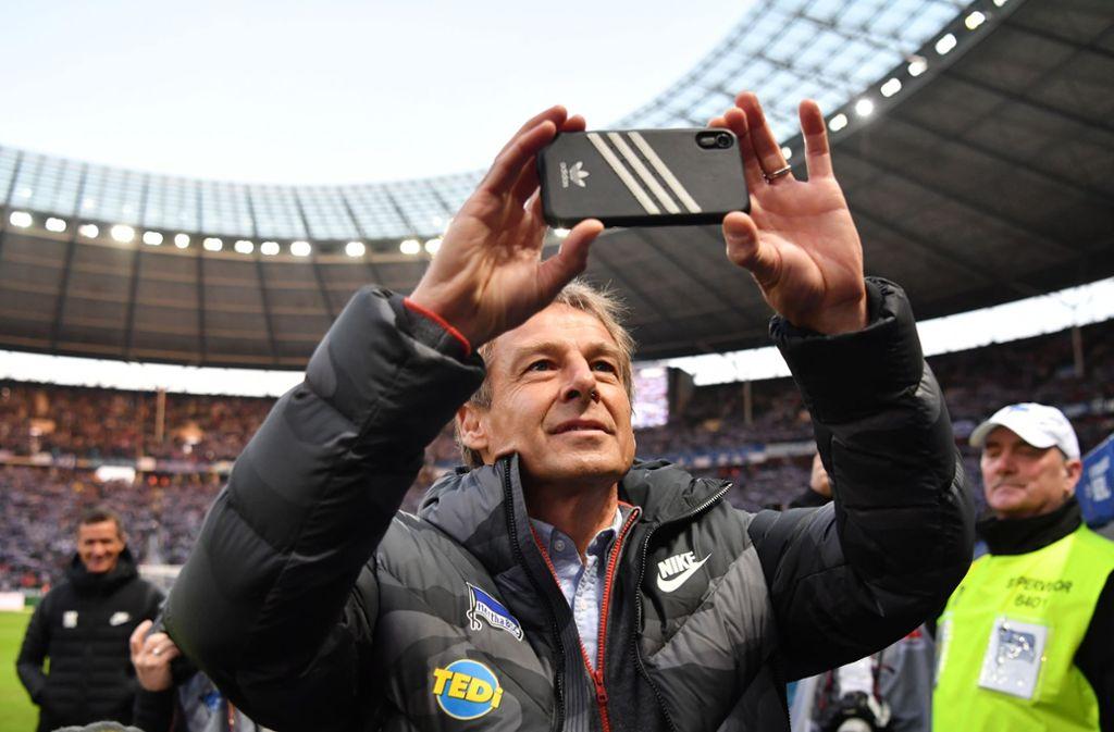 Jürgen Klinsmann filmt mit seinem Smartphone vor dem Spiel im Stadion von Hertha BSC Berlin. Foto: Bernd König/Bernd König