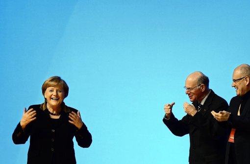 Norbert Lammert und Volker Kauder bejubeln die Kanzlerin. Foto: dapd