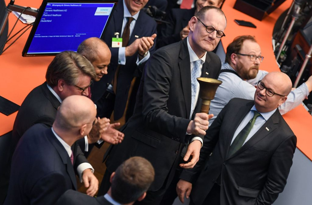 Bernd Montag,  Vorstandsvorsitzender der Siemens Healthineers AG, schwingt auf dem Parkett der Frankfurter Wertpapierbörse die Börsenglocke. Foto: dpa
