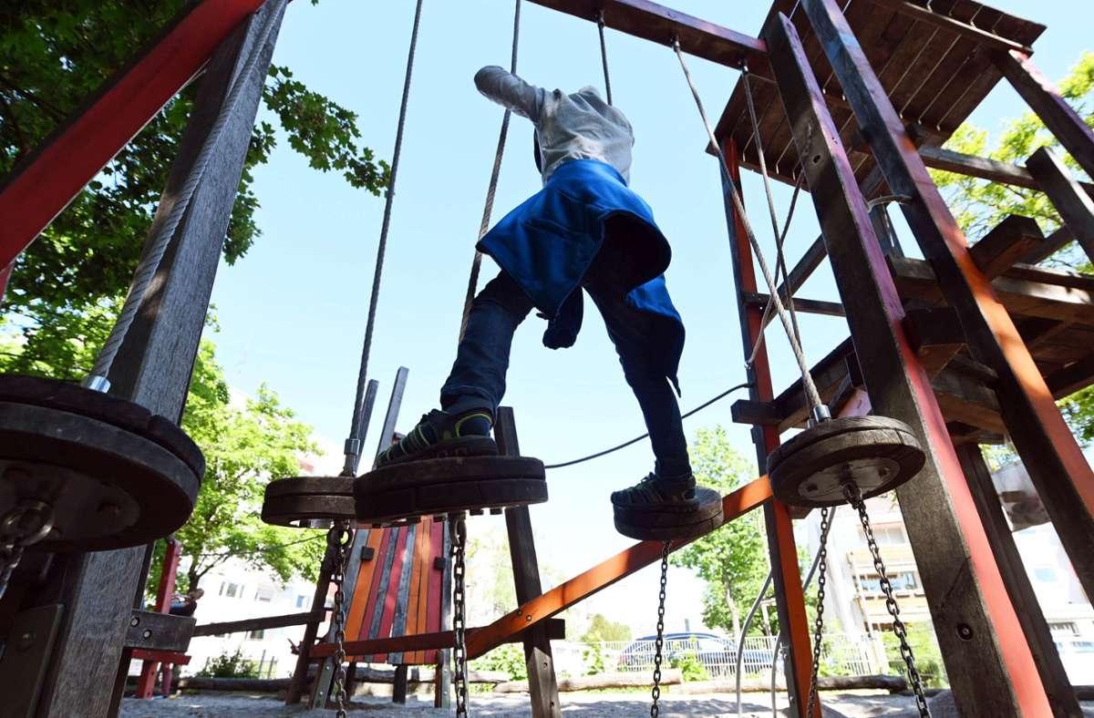 Ein Kind geht auf einem Spielplatz über einen Kletterparcours. Foto: Uli Deck/dpa