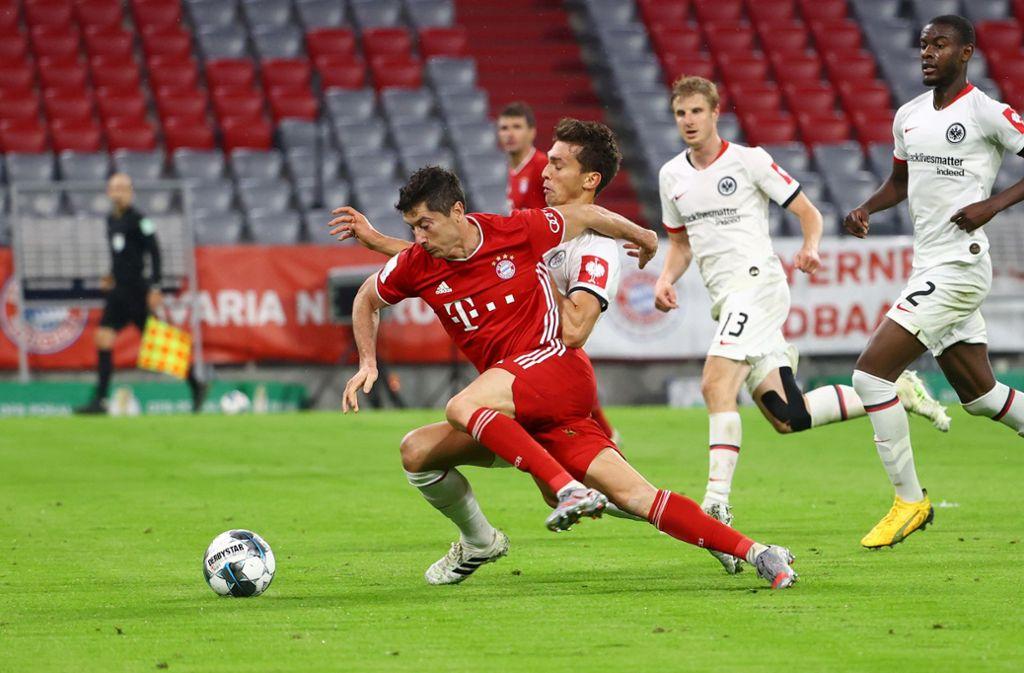 Bayern Münchens Robert Lewandowski  in Aktion gegen Frankfurts Verteidiger. Foto: dpa/Kai Pfaffenbach