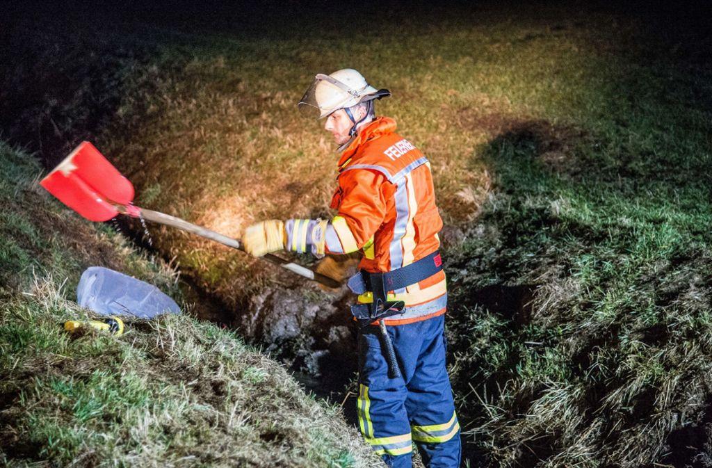 Die Einsatzkräfte dämmen die grüne Substanz im Fluss ein. Foto: SDMG