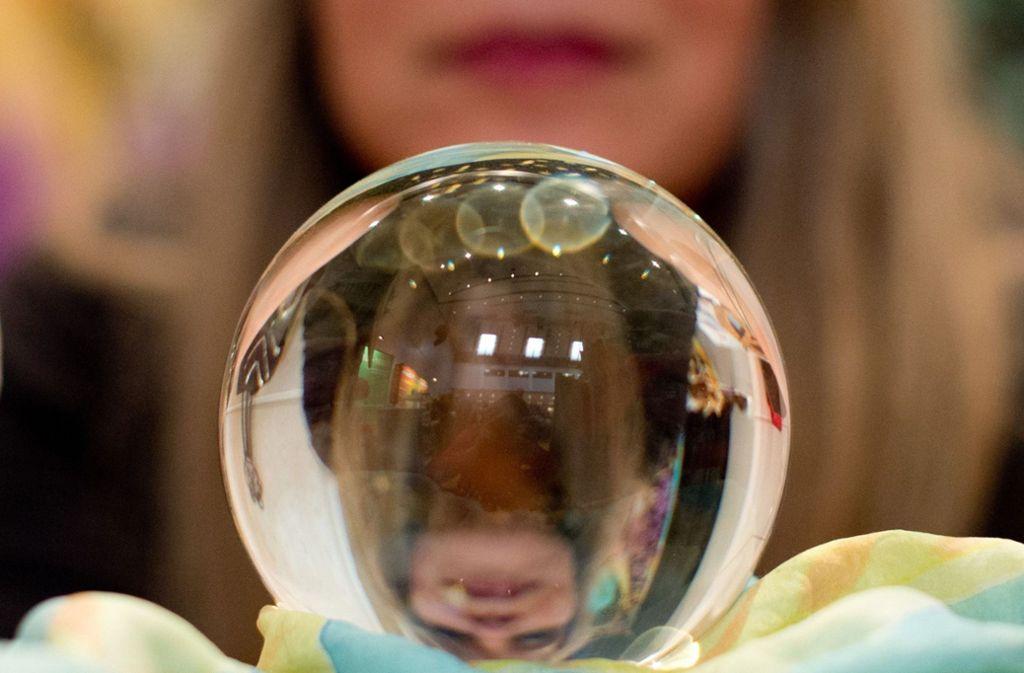 Eine Wahrsagerin blickt auf der Esoterik-Messe in Stuttgart in eine Kristallkugel (Symbolbild) Foto: dpa/Sebastian Kahnert