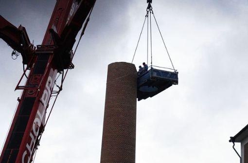 Arbeiter bauen 50 Meter hohen Kamin per Hand ab