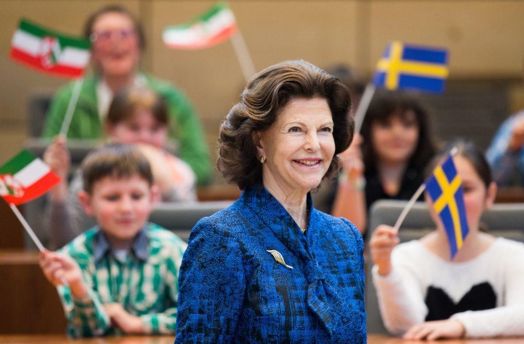 Begrüßung mit Fähnchen: Viertklässler aus Köln und dem bergischen Burscheid dürfen die Königin treffen und einige Fragen an die 72-Jährige richten.  Foto: dpa