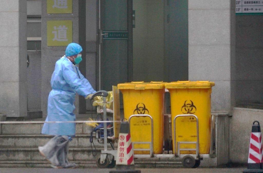 Ein Mitarbeiter eines Krankenhauses in der chinesischen Metropole Wuhan entsorgt Container mit Sondermüll. Foto: AP/Dake Kang