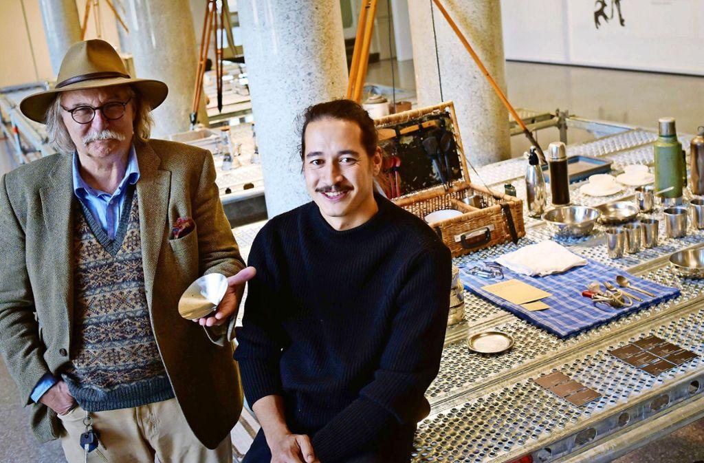 Eberhard Holder und Micha Klein mit ihrer Ausstellung und einem faltbaren Trinkbecher. Foto: Lichtgut/Max Kovalenko